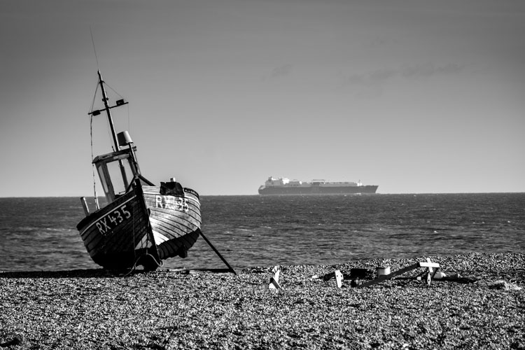 Boat on the shoreline with a tanker in the distance juxtaposed