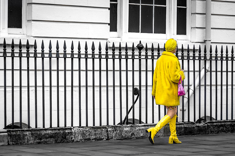 Woman dressed all in yellow on a black and white street