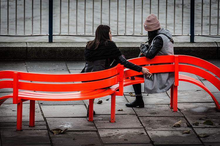Two women sitting on bright orange street furniture talking