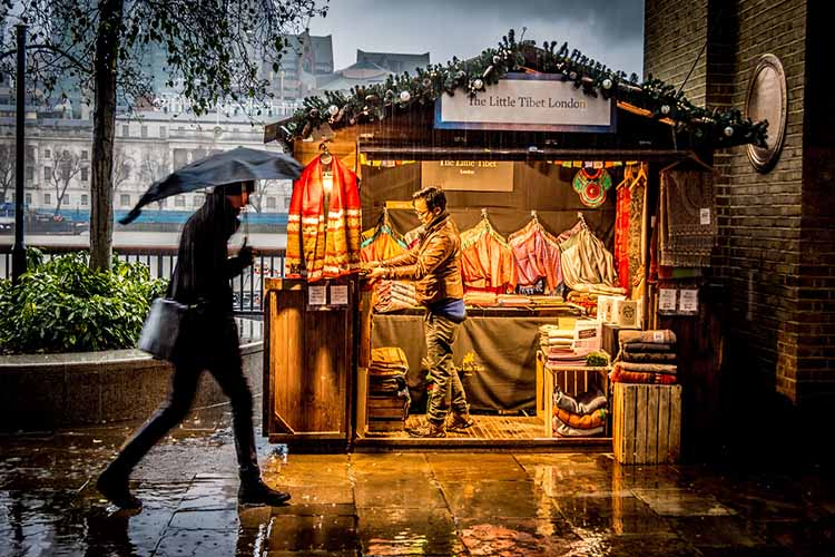 Man walking past a lit up pop up shop in the rain