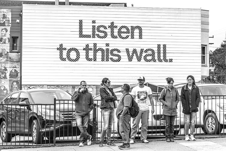 "People standing in front of a billboard with the text ""Listen to this wall"""