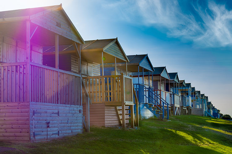 Colourful beach huts with a lens flare