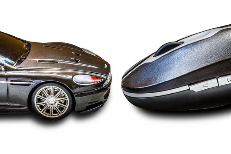 Aston Martin DB7 diecast model facing a computer mouse